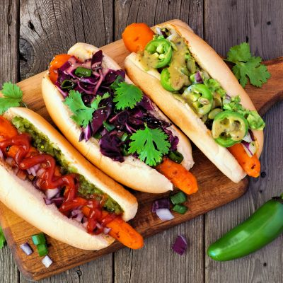 Carrot hot dogs with assorted toppings. Top view on paddle board with a rustic wood background. Plant based vegan meal concept.